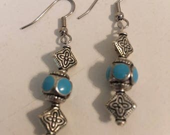 Metal and turquoise colored earrings