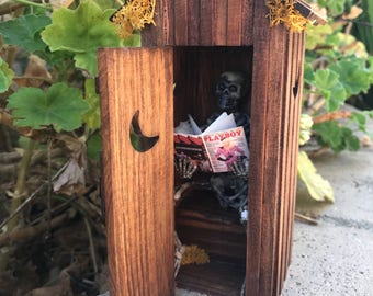 Playboy Reading Skeleton in Outhouse