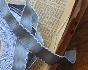 25 yard roll of pewter grosgrain ribbon with white scalloped stitched edge