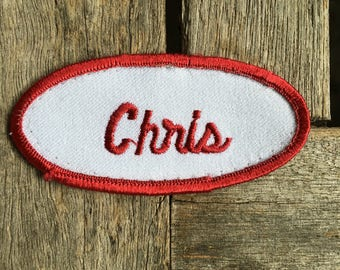 "Chris Name Patch. A white work shirt name patch with ""Chris"" in red script with red border."