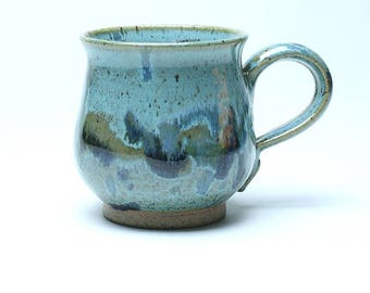 Turquoise stoneware mug with abstract multi-glaze pattern.