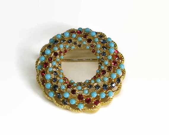 Large multi stone circular brooch, open metal work, studded with red and blue rhinestones and turquoise beads, circa 1980s