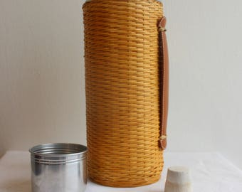 Vintage thermos bottle covered in wicker with tin top and lid