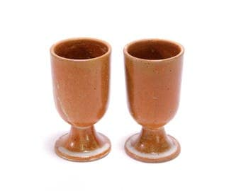 A pair of terracotta colored stoneware wine glasses