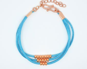 Multi strand turquoise leather and rose gold plated spacer bead bracelet with S hook clasp and adjustable extender chain