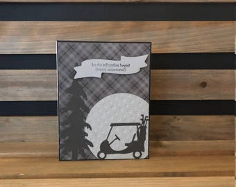 Golf Themed Retirement Card! Gray and Black Plaid Background, Die Cut Golf Cart and Tree, White Embossed Golf Ball and Sentiment