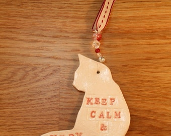 Keep Calm and Meow On. Pottery Cat Ornament with white and red glazes. Sent to you in a white gossamer bag.