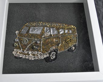 Volkswagen made out of watch parts set in a white boxed frame