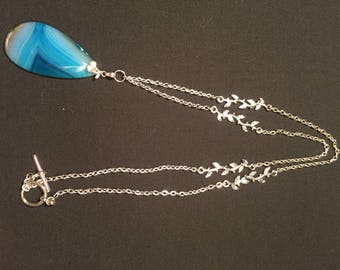 Silver chain with leaf sections and multi hued blue focal bead