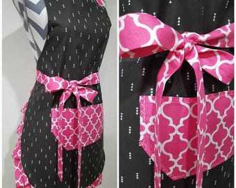 Adult apron. Woman's apron. Blackish gray with white arrows on main with pink on pocket, ties and frills.