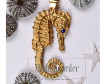 Gold seahorse pendant with sapphire eyes