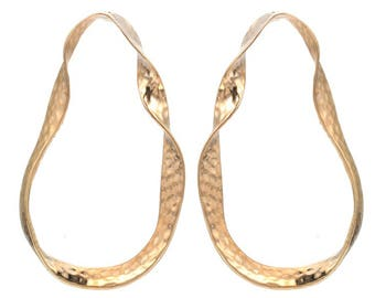 Dramatic twisted hoop earrings, textured effect, minimalist and modern.