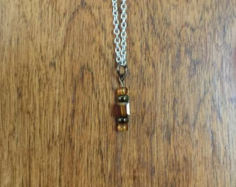 Small, square amber glass bead with amber and brown hematite beads pendant