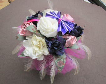 fabrics, feathers, beads with a vase arrangement