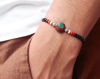 18.5 CM. Black beaded bracelet with brass bell and amber  ByMartinversaz