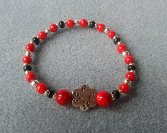 Red and black bracelet with a silver metal flower