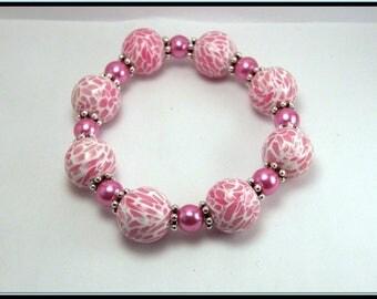 Bracelet élastique perle mozaïque rose en fimo et perle en verre.