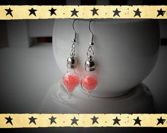 globe-shaped drop in a glass filled with sandblasted coral earrings