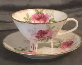 Beautiful vintage cup and saucer with feet.
