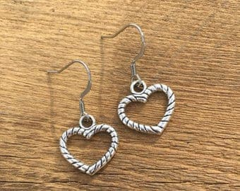 Silver tone open heart earrings on stainless steel wires.