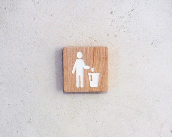 Wooden sign with engraved pictogram to indicate the trash bin