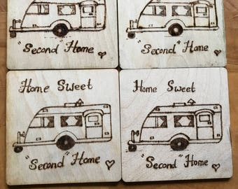 """4 wooden coaster with a picture of a caravan wood burned on with the caption """"Home Sweet Second Home"""" on."""