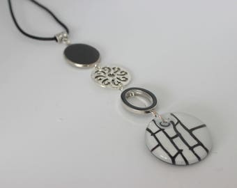 Original vertical necklace in black and silver metal with black and white piece of glass.