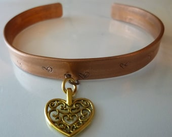 Queen of Hearts copper bracelet with small hearts stamped on the band and a brass heart handing from the front