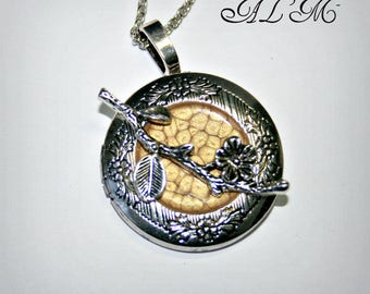 Pendant is picture with flower and branch and background antique gold