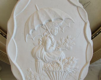 Vintage French  plaster/chalk plaque. Young lady under a parasol and framed with a bow