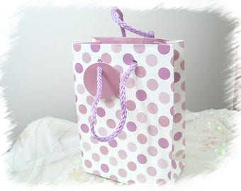 White gift bag has pink polka dots in glossy paper