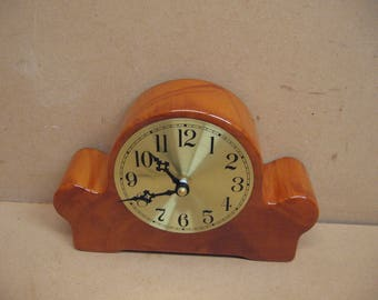 Cypress mantel clock with a brass face.