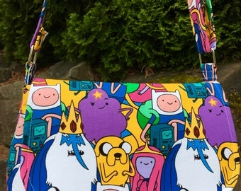 Adventure Time Packed Characters cross-body/shoulder/saddle bag with exterior zipper, 2 slip pockets, adjustable strap