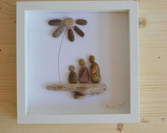 Beach pebble family under a flower framed art