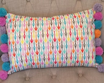 Handmade, colourful, 18x12inch rectangular cushion trimmed with Merino wool Pom poms. Original design, 100% cotton fabric.