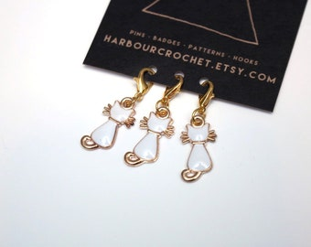 Set of 3 cat shaped stitch markers; gold toned metal with white enamel detail, on lobster clasps