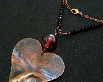 Necklace with heart pendant in beaten copper and red and black beads.