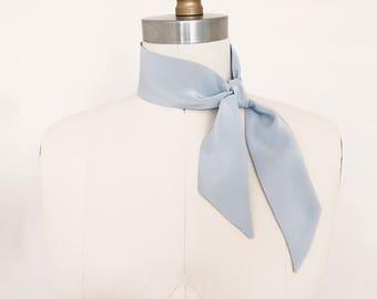 "Silk kerchief in pale blue stone. 33""x2"" Easy care silk scarf to wear as a bandana, ascot neck-tie, hair tie or choker in faded denim blue."