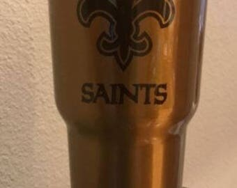 30 oz candy gold yeti with New Orleans Saints engraved on it