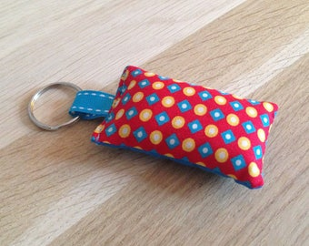 Fabric, red, blue and yellow keychain.