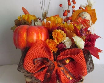 Autumn Themed Silk Flower Arrangement in a Multi-colored Basket, Featuring Pumpkin, Scarecrow Pick, and a Handmade Bow