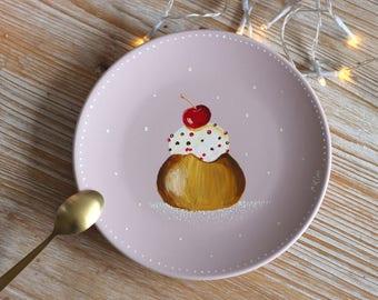 Petite assiette à desserts de couleur rose peinte avec un Baba au rhum