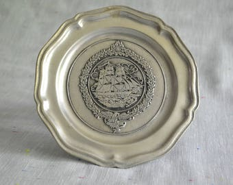Decorative pewter plate features USS Constellation in Baltimore
