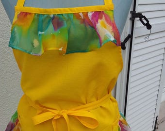 Sun cotton apron has multi colors printed synthetic ruffles and two pockets with ruffle