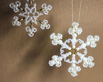 Set of delicate snowflakes handmade for the Christmas tree. Ornament of their white shimmeri pearls. Winter festive decoration.