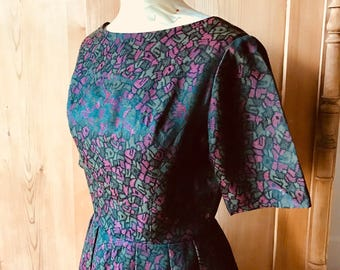 Festive 1950s green and magenta floral brocade dress.