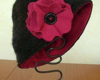 Black fur hat adorned with a pretty red flower