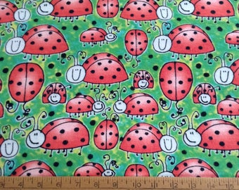 Flannel ladybugs on green background cotton fabric by the yard