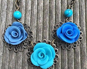 very light necklace featuring three blue roses