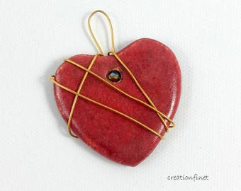 A gold plated wire wrapped red heart